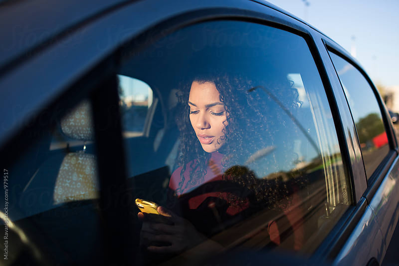 Businesswoman using her cell inside a car  by michela ravasio for Stocksy United