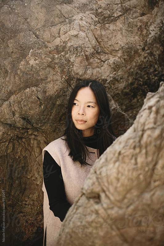 fashionable asian woman standing between rocks on coast by Nicole Mason for Stocksy United