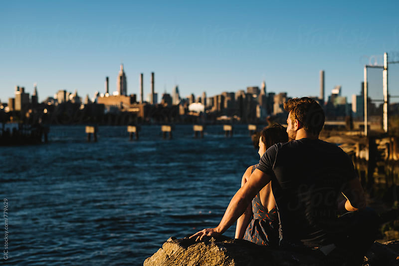 Young couple sitting against NY skyline by GIC for Stocksy United