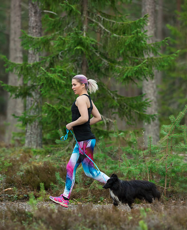 jogging woman and dog by Andreas Gradin for Stocksy United