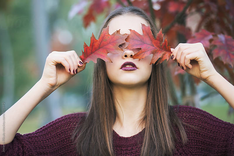 Autumn portrait of a beautiful young woman holding leaves by Jovana Rikalo for Stocksy United