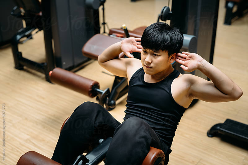 Man doing sit-ups in gym by Maa Hoo for Stocksy United