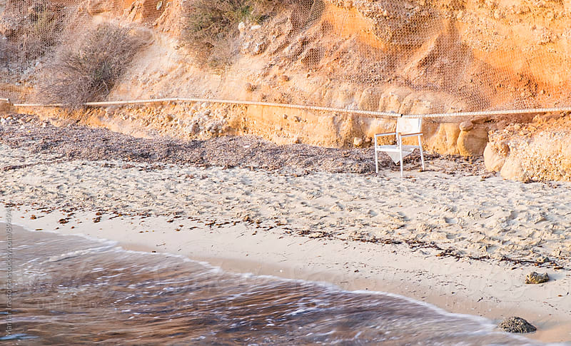 Abandoned chair on a beach by Marilar Irastorza for Stocksy United