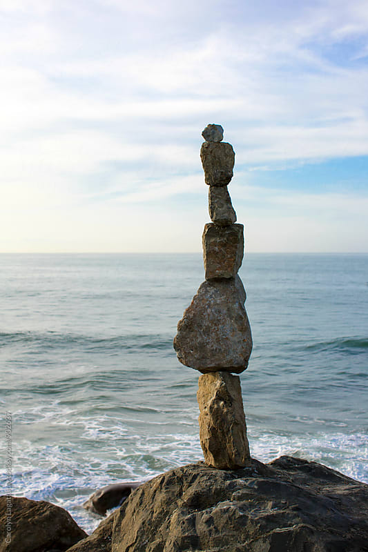Stacked rocks overlooking the ocean by Carolyn Lagattuta for Stocksy United