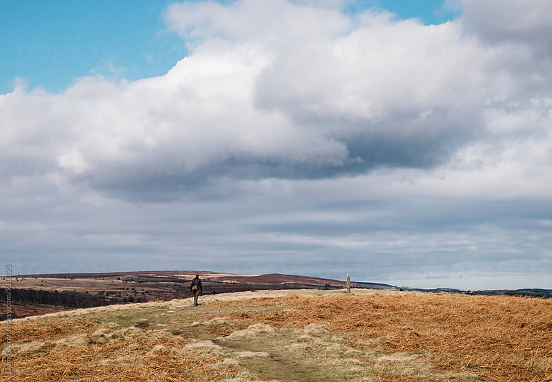 Male walking near the stone cross on Ramsley Moor. Derbyshire, UK. by Liam Grant for Stocksy United