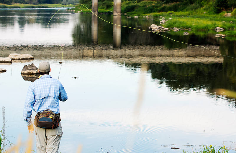 A young man at the bank of the river with the fly fishing pole.  by Tana Teel for Stocksy United