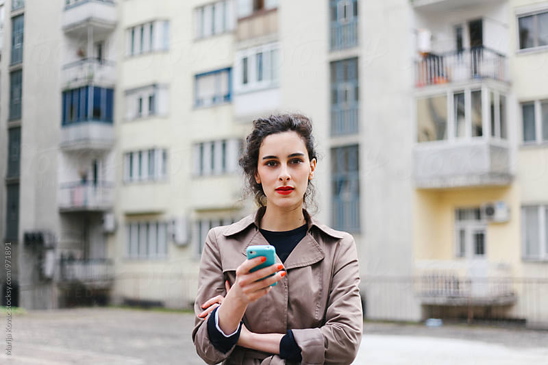 Pretty woman looking at the camera, holding a cell phone by Marija Kovac for Stocksy United