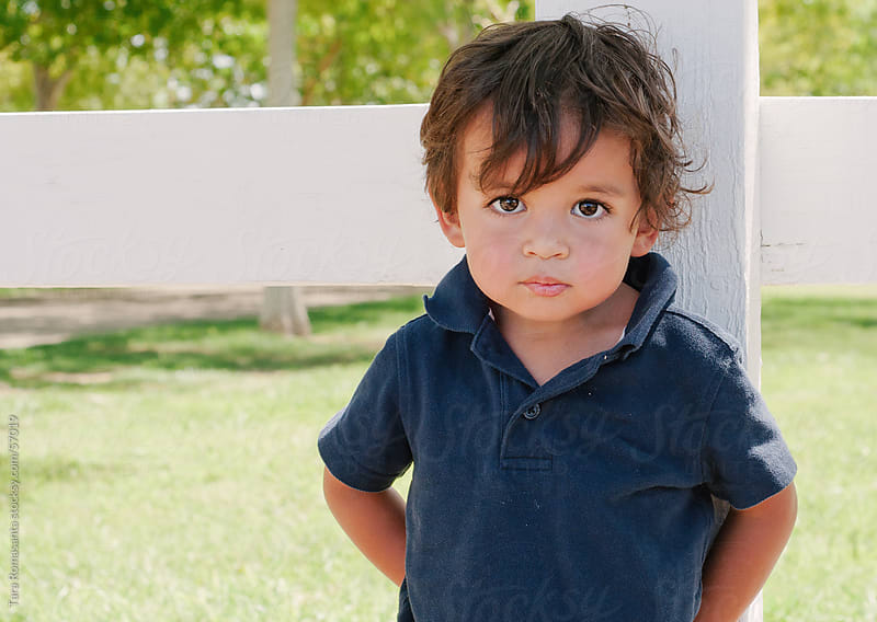 toddler mestizo boy stands by a fence by Tara Romasanta for Stocksy United