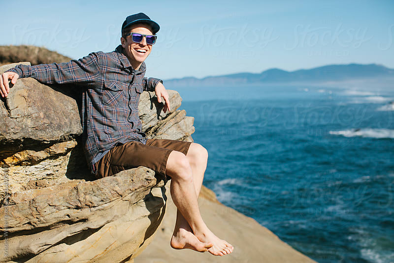 Man sitting on a rock with the ocean in the background by Kristine Weilert for Stocksy United