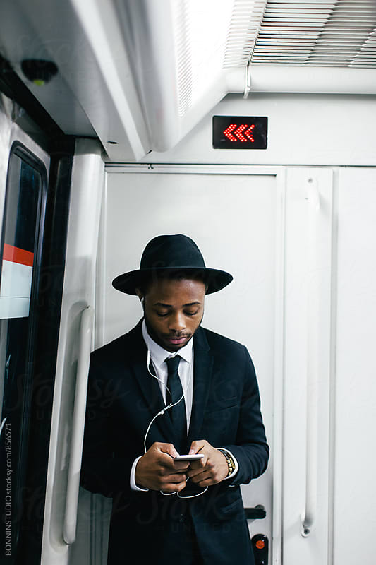 Businessman listening music whilst using his phone on subway. by BONNINSTUDIO for Stocksy United