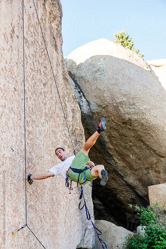 Young man playing and having fun while rock climbing by Alejandro Moreno de Carlos for Stocksy United