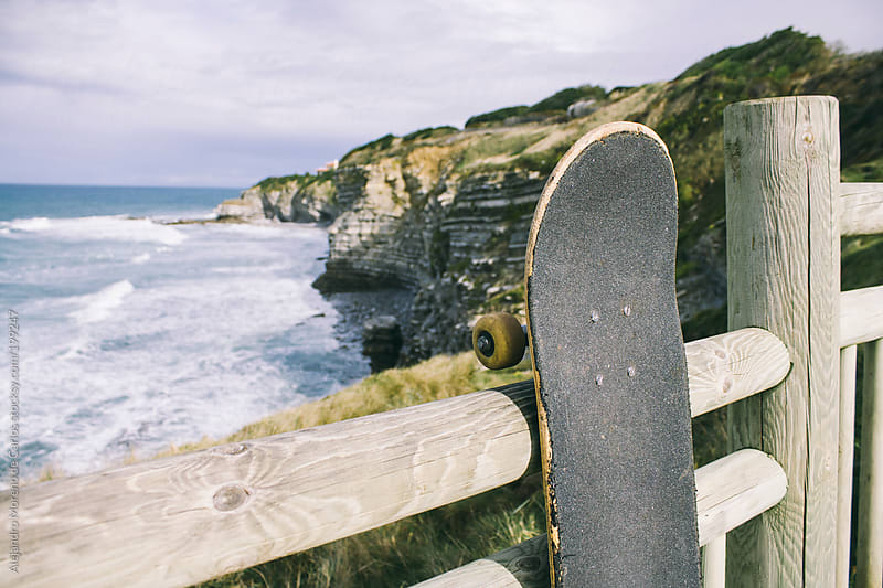 Skateboard hanged on a wood gate next to the coast by Alejandro Moreno de Carlos for Stocksy United
