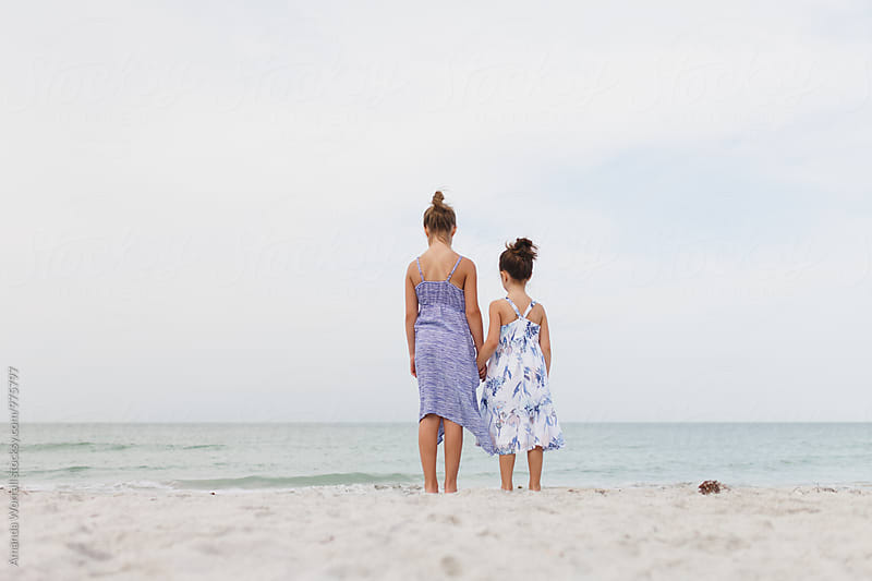 Two young girls standing on the beach holding hands by Amanda Worrall for Stocksy United