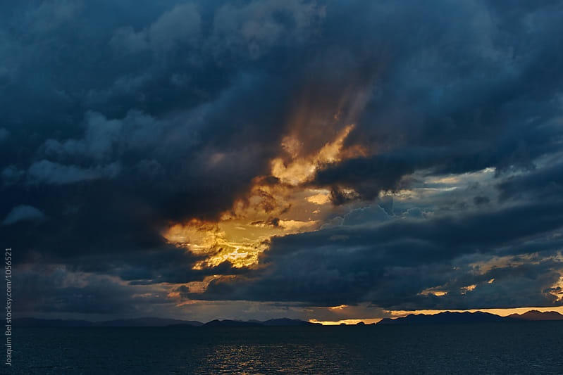 Sun strikes thru a cloudy sky by Joaquim Bel for Stocksy United