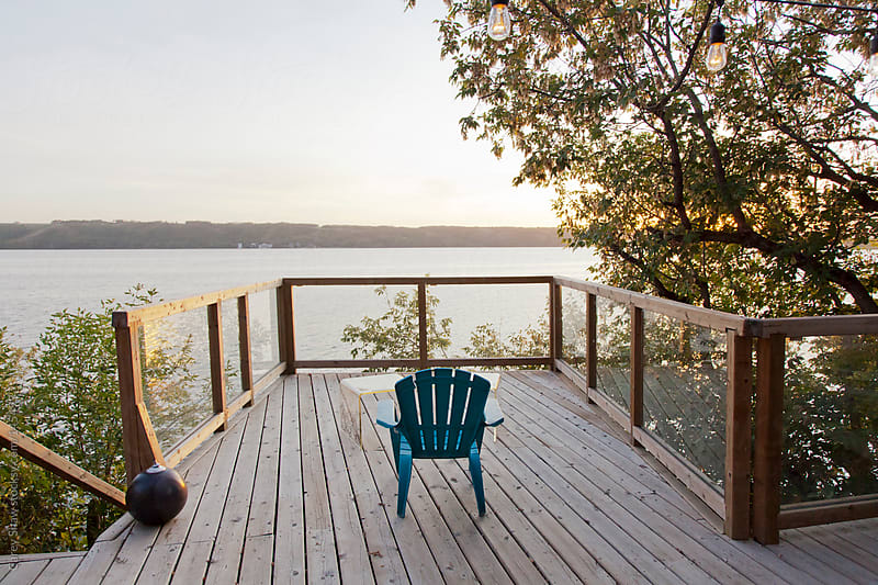 Lakefront patio with a single blue chair by Carey Shaw for Stocksy United