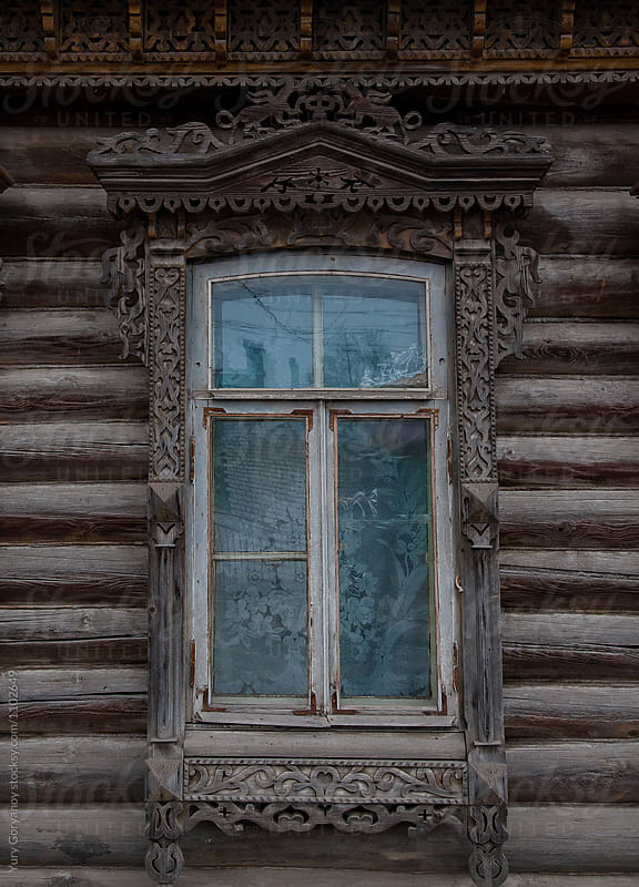 Window of an old Russian house with carved architraves by Yury Goryanoy for Stocksy United