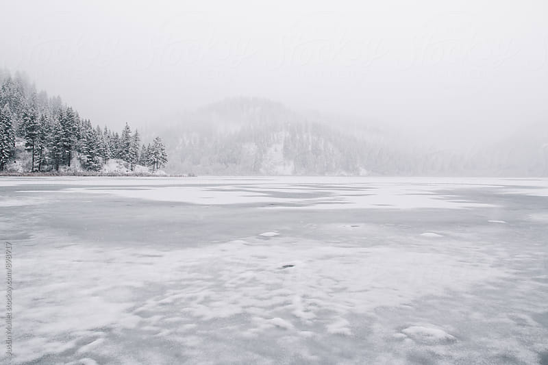 A frozen lake on a gray snowy day by Justin Mullet for Stocksy United
