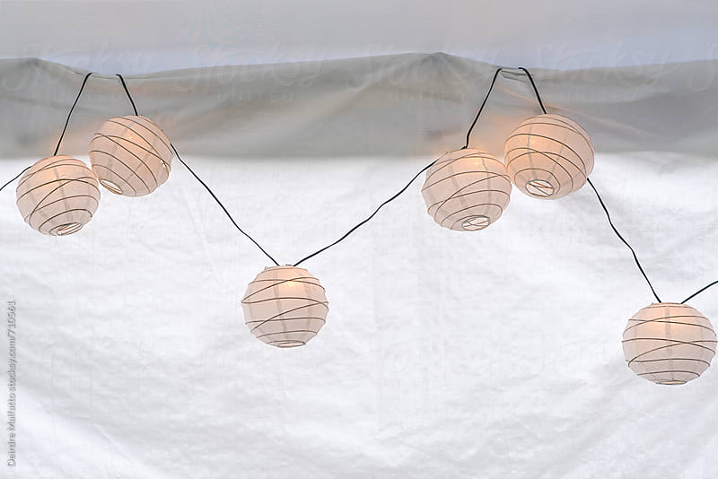 string of glowing paper lanterns on white background by Deirdre Malfatto for Stocksy United