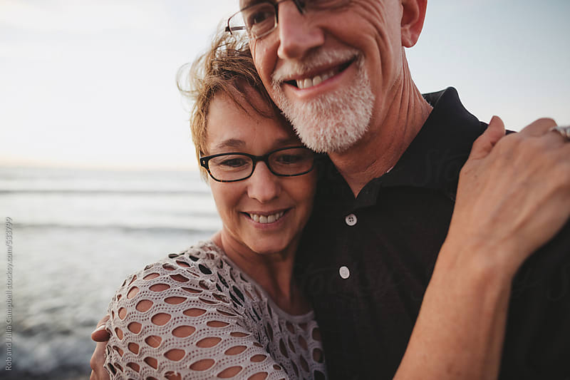 Content middle aged, retired couple hug together outside on ocean beach by Rob and Julia Campbell for Stocksy United
