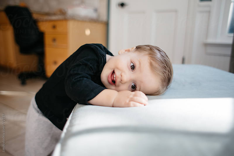 Cute toddler boy leaning his head on an ottoman by Jakob for Stocksy United