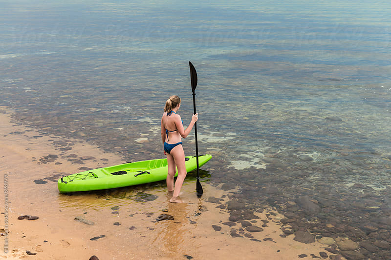 teen girl with kayak and paddle at the beach by Gillian Vann for Stocksy United