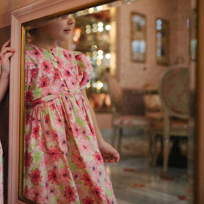 Little girl in party dress seen reflected in a mirror. by Julia Forsman for Stocksy United