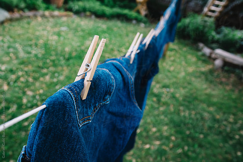 Blue jeans hung out to dry by Gabriel (Gabi) Bucataru for Stocksy United