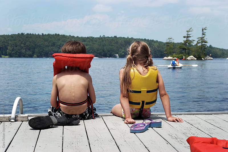 A young boy and girl wearing life vests sit at the edge of a dock on a lake  by Cara Dolan for Stocksy United