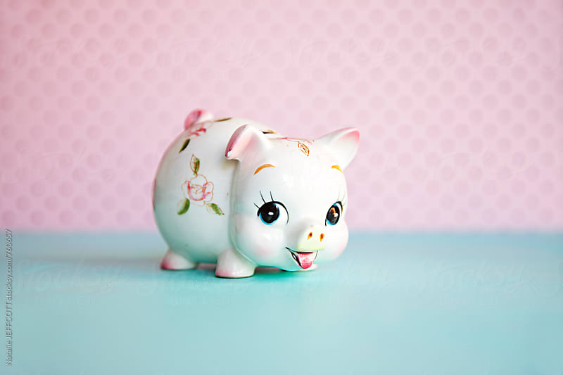 cute piggy bank money box against blue and pink colours by Natalie JEFFCOTT for Stocksy United