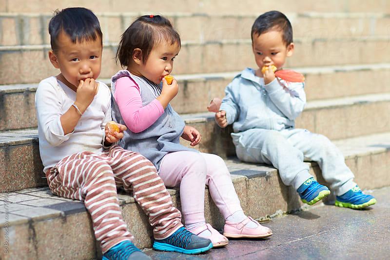 three little kids eating by Bo Bo for Stocksy United