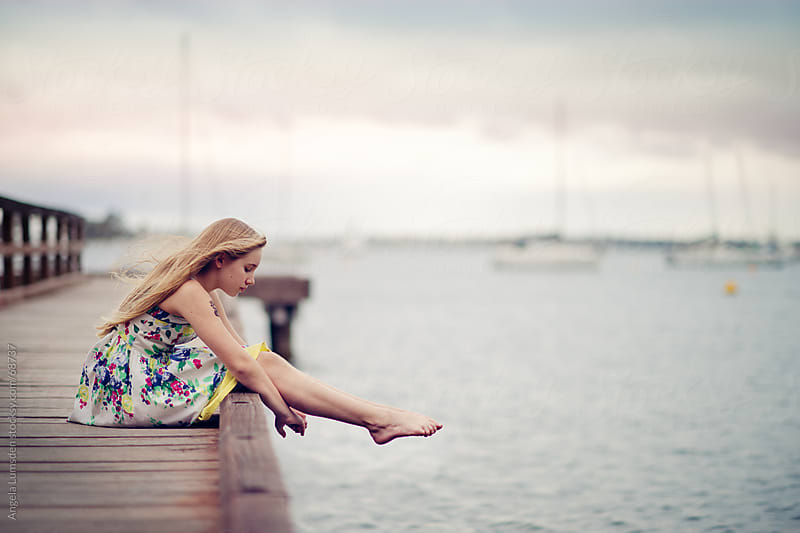 Girl sitting on a dock on a cloudy day by Angela Lumsden for Stocksy United