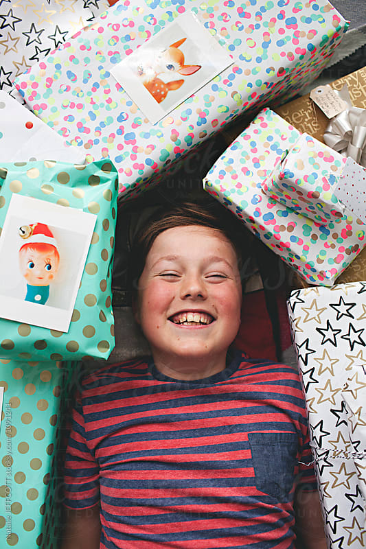 A young boy lying on floor surrounded by Christmas presents by Natalie JEFFCOTT for Stocksy United
