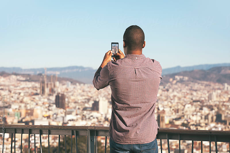Black young man taking a photo of Barcelona panorama with his mobile phone.  by BONNINSTUDIO for Stocksy United