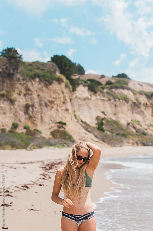 Young Woman with Long Blond Hair Standing on a Beach in her Bekini by Briana Morrison for Stocksy United