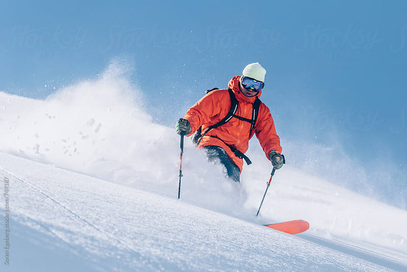 Skier wearing red jacket skiing powder snow in the mountains by Soren Egeberg for Stocksy United