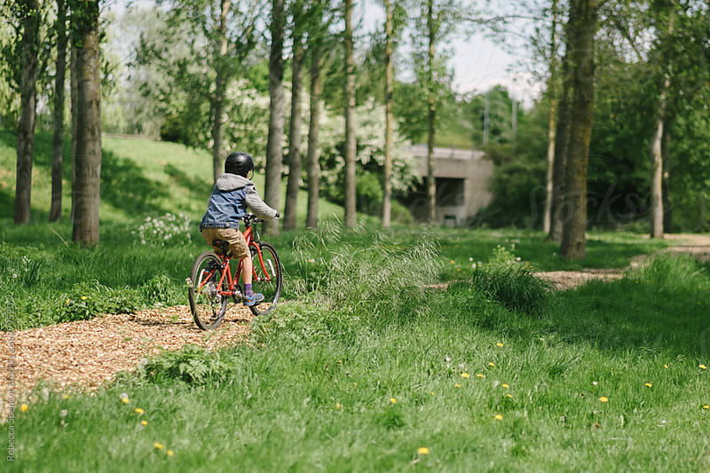Child cycling along a rural path towards an underpass by Rebecca Spencer for Stocksy United