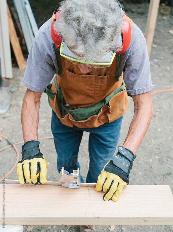 Elderly woman carpenter measuring lumber with a square by Mihael Blikshteyn for Stocksy United