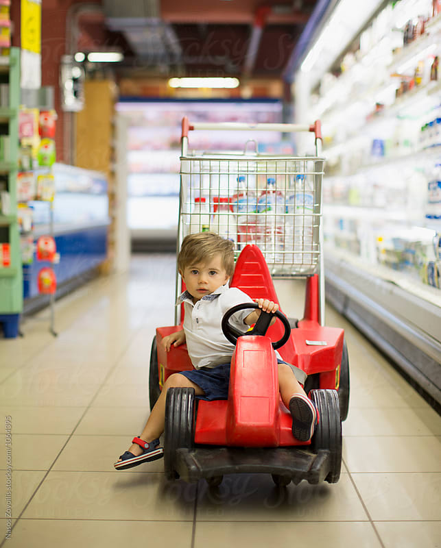 1 year old boy sitting in the shopping cart in a supermarket by Nasos Zovoilis for Stocksy United