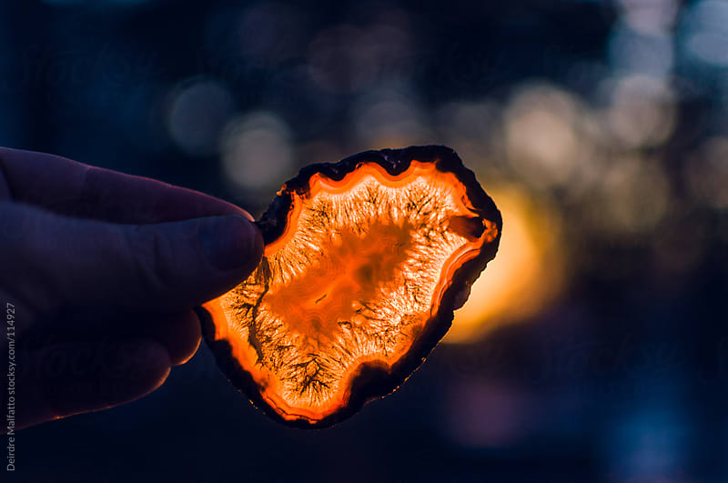 slice of gold agate held in front of setting sun by Deirdre Malfatto for Stocksy United