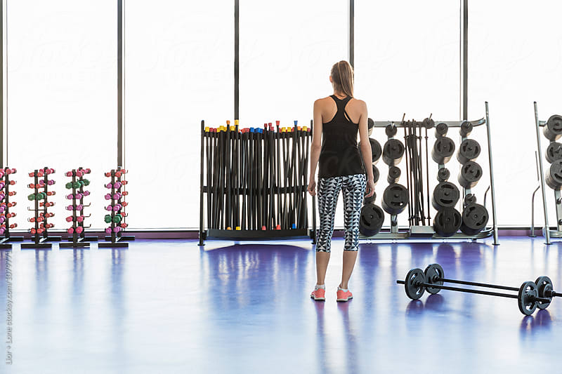 Woman athlete looking at weights in a studio by Lior + Lone for Stocksy United