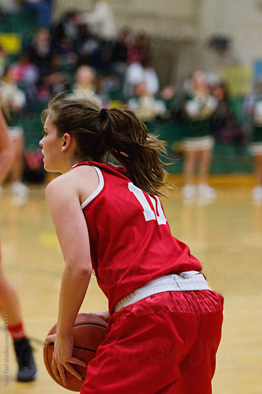 female basketball player holds basketball during game by Tana Teel for Stocksy United