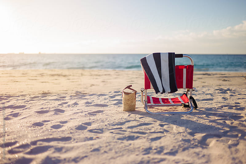 Beach chair on sand at ocean edge by Angela Lumsden for Stocksy United