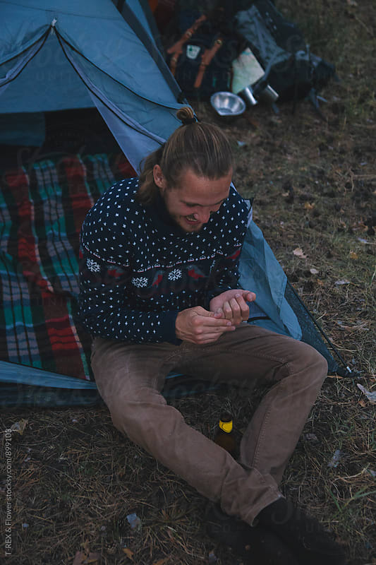 Young blond man in sweater sitting near tent by Danil Nevsky for Stocksy United