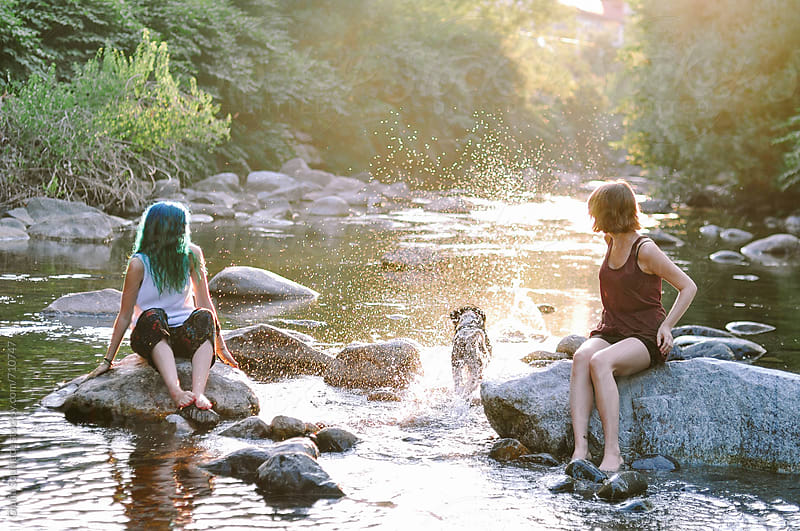 Young women playing with a dog in the river by Giulia Squillace for Stocksy United