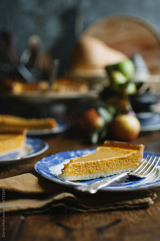Slice of pumpkin pie on a blue plate on wooden table, selective focus. by Darren Muir for Stocksy United