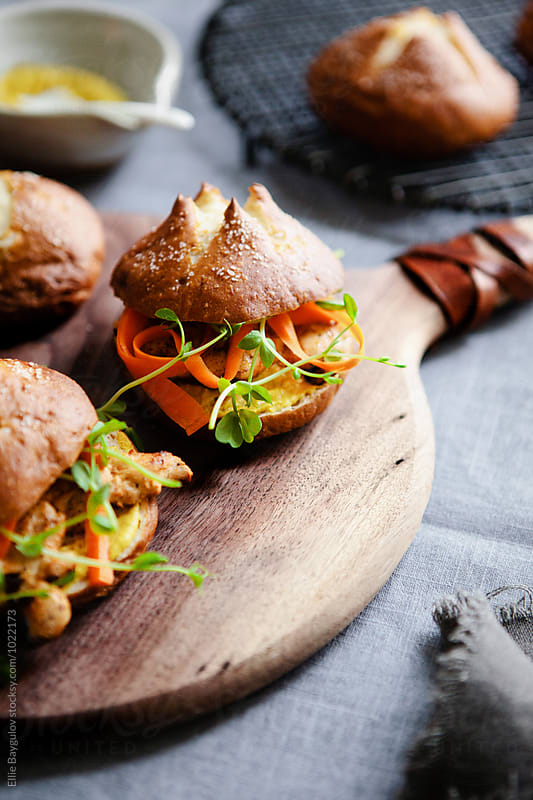 Grilled chicken sandwiches on pretzel buns by Ellie Baygulov for Stocksy United