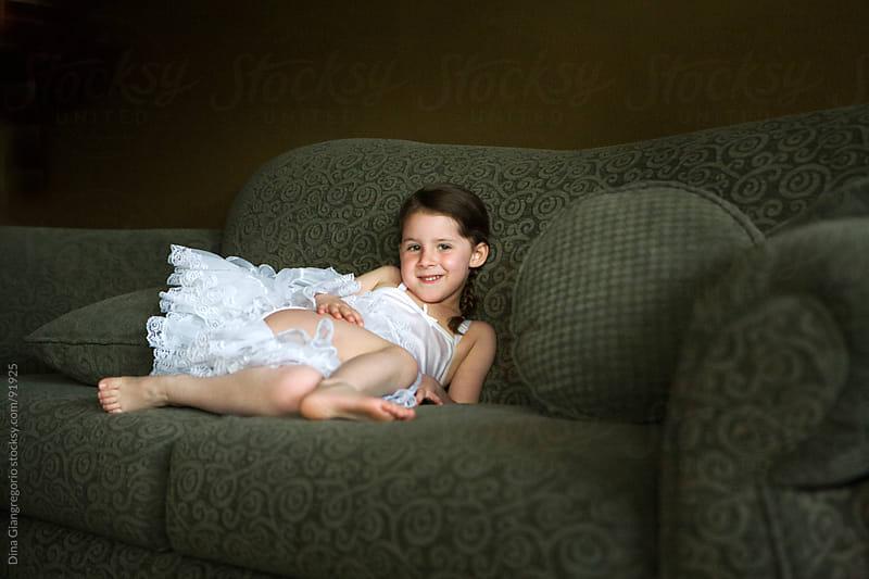 Little girl in white slip dress relaxing on green couch by Dina Giangregorio for Stocksy United