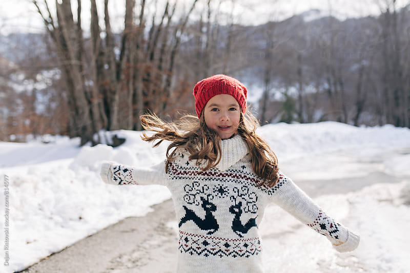 Girl playing on snow by Dejan Ristovski for Stocksy United