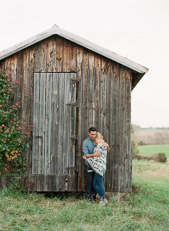 Couple posing in front of an old wood shed by Marta Locklear for Stocksy United