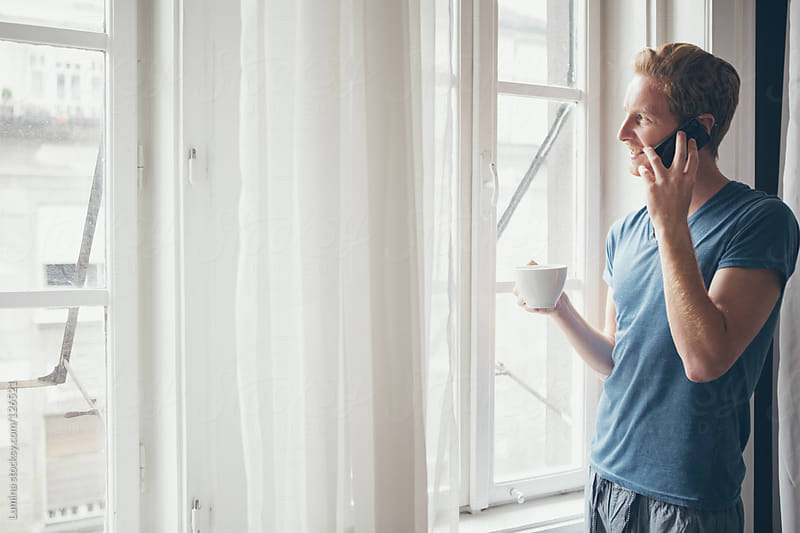 Young Man Telephoning by the Window by Lumina for Stocksy United